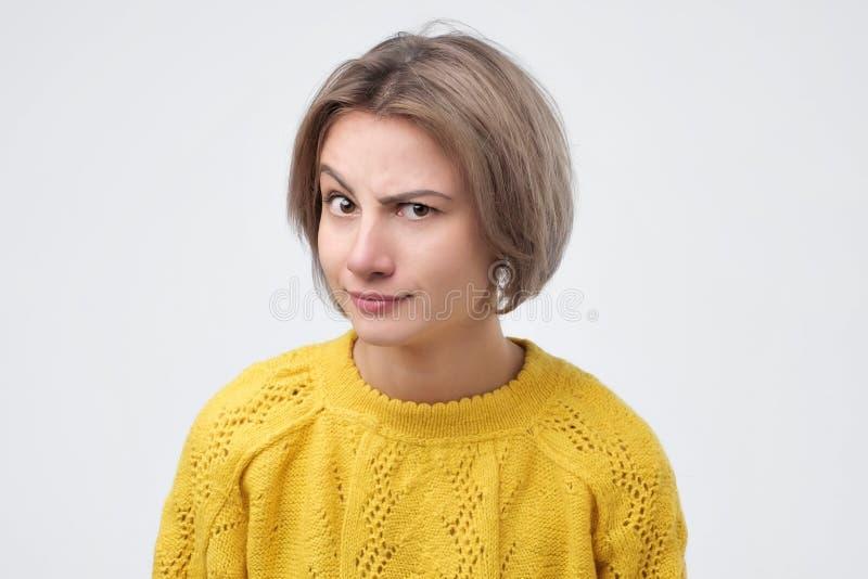 Hübsche junge kaukasische Frau in der gelben Strickjacke mit einem neugierigen Ausdruck stockbilder