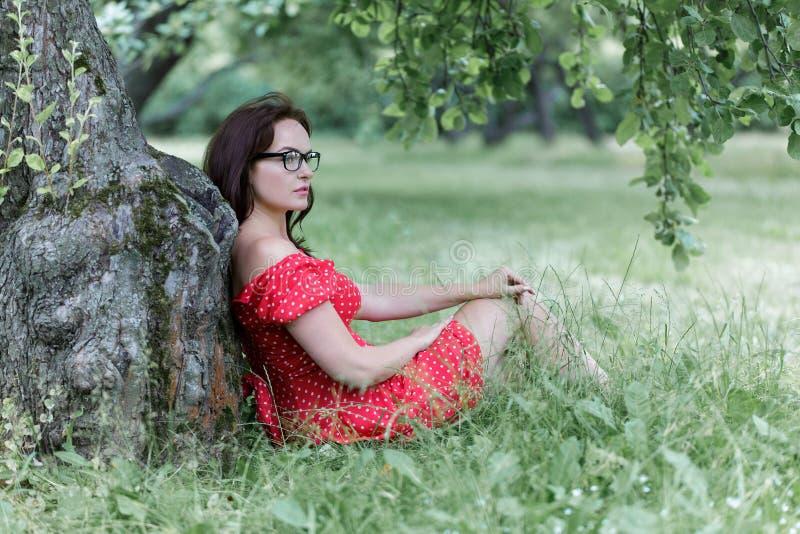 H?bsche junge kaukasische Frau, die drau?en unter einem Baum sich entspannt stockbild