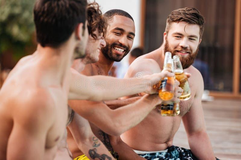 Hübsche junge lächelnde Männer, die Spaß im Swimmingpool haben stockbilder