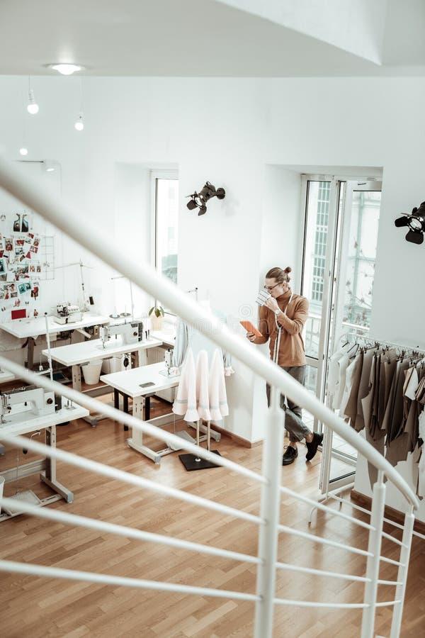 Hübsche junge ModedesignerFormulargenerierung Y, die entspannt schaut lizenzfreie stockfotografie