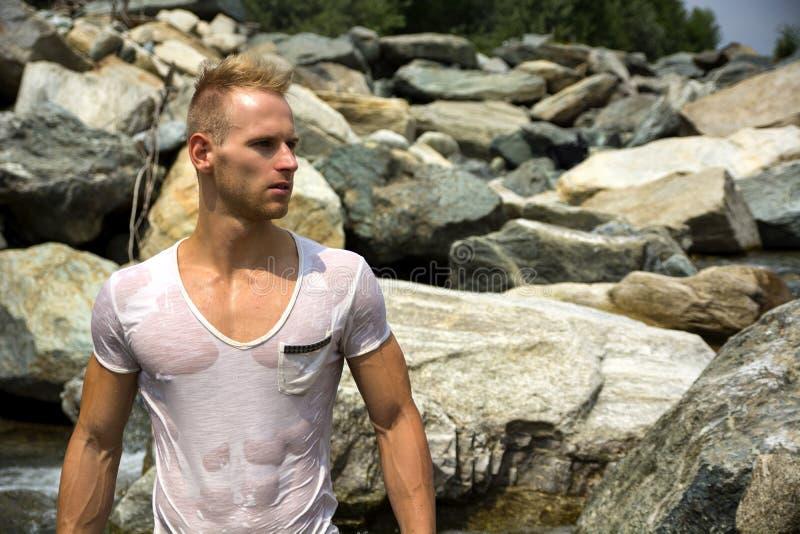 Hübsche junge Muskelmannstellung, tragendes nasses weißes T-Shirt lizenzfreie stockbilder