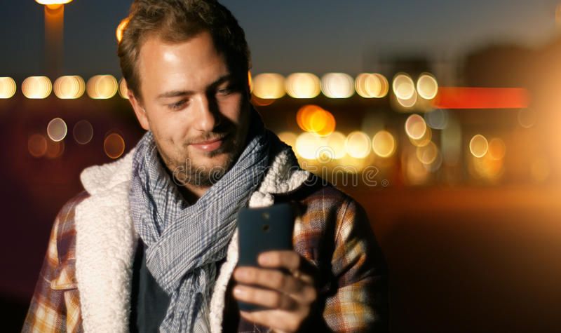 Hübsche junger Mann sms, die unter Verwendung APP am intelligenten Telefon am autum simsen stockfoto