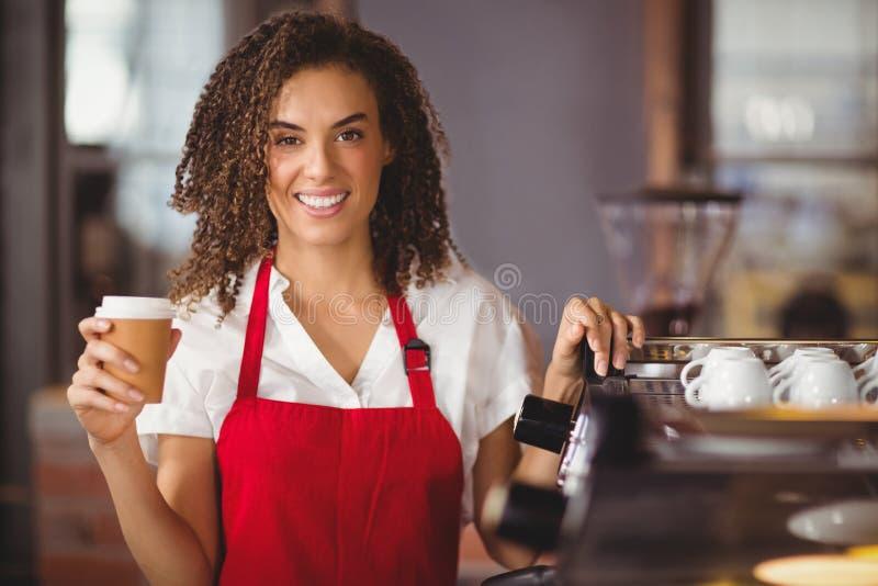 Hübsche Kellnerin, die einen Mitnehmerbecher hält stockfoto