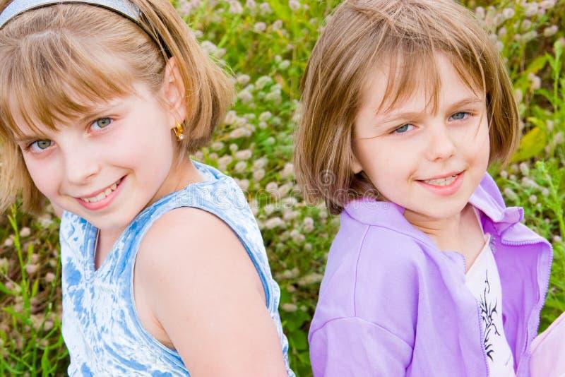 Hübsche Kinder und Jugendlichmädchen auf grünem Gras stockfotos