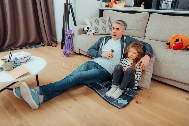Hübsche kleine Tochter mit Augenklappen und ihr Vater, der ernst schaut lizenzfreie stockfotografie