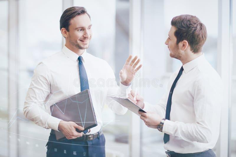 Hübsche Kollegen, die über Arbeit sprechen stockfoto