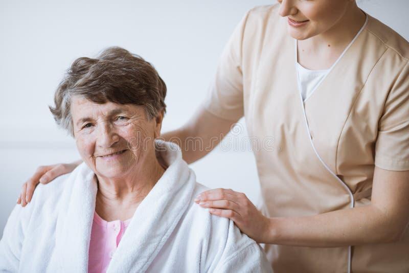 H?bsche Krankenschwester der Rothaarigen in der beige Uniform mit ihren H?nden auf ?lteren Frauenschultern stockbilder