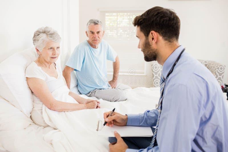 Hübsche Krankenschwester, die eine reife Frau besucht lizenzfreie stockfotos