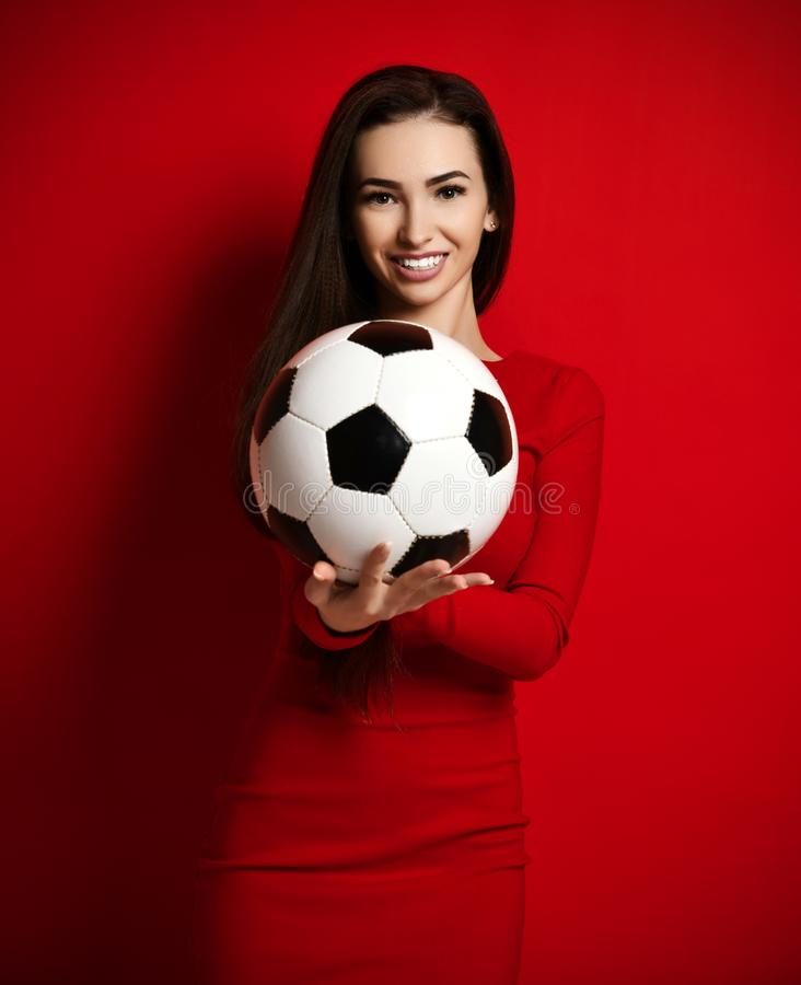 Hübsche lächelnde brunette Frau im festen roten Kleidergrifffußball in den Händen auf Rot lizenzfreie stockfotos