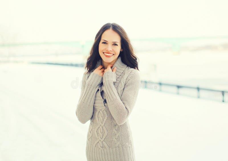 Hübsche lächelnde Frau des Porträts, die draußen eine gestrickte Strickjacke im Winter trägt stockfoto