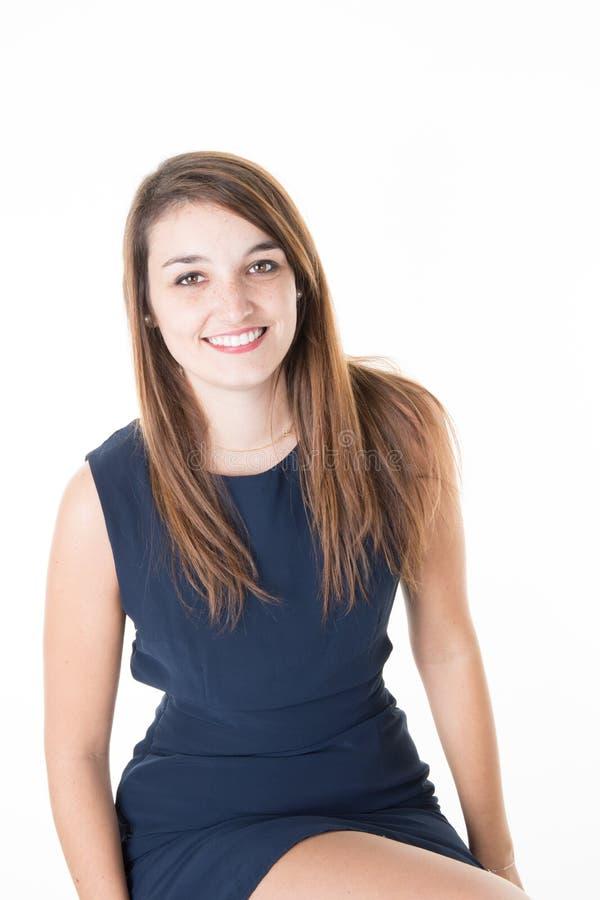 Hübsche lächelnde Frau, die das Sitzen lokalisiert auf einem weißen Hintergrund aufwirft stockfotografie