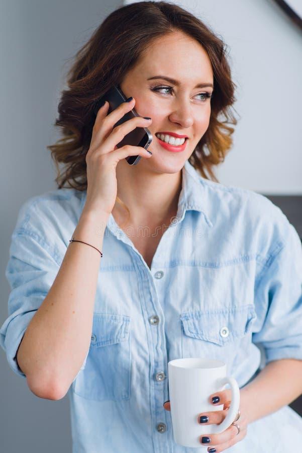 Hübsche lächelnde Frau, die an einem Handy spricht und eine Schale hält stockfotos