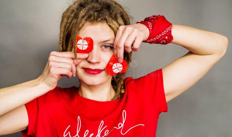 Hübsche lächelnde Frau mit Dreadlocks und rote Lippen mit einem roten Herzen des Origamis, für Valentinsgruß ` s Tag stockfotografie