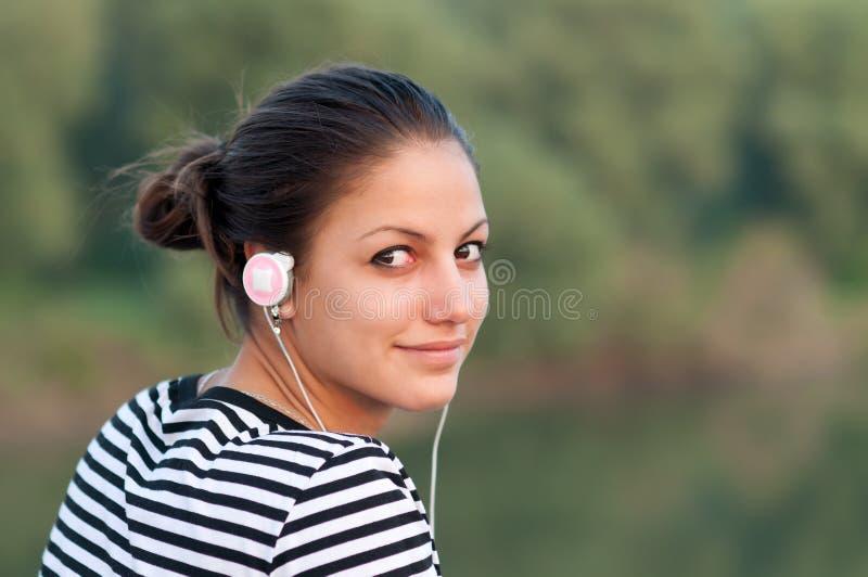 Hübsche lächelnde Jugendliche hört Musik stockbild