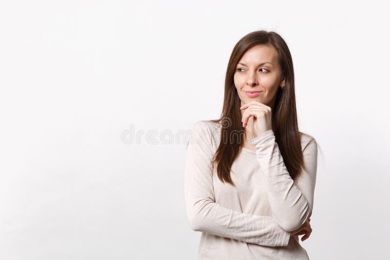 Hübsche lächelnde junge Frau in der hellen Kleidung, die beiseite schaut, setzte Hand sützen auf dem Kinn, das auf weißem Wandhin lizenzfreie stockfotografie
