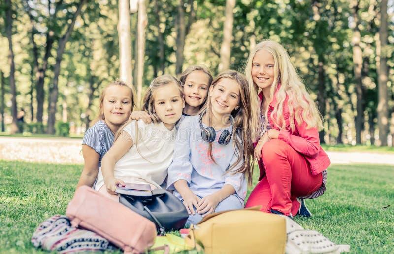 Hübsche lächelnde kleine Mädchen sitzen zusammen im Park lizenzfreies stockbild