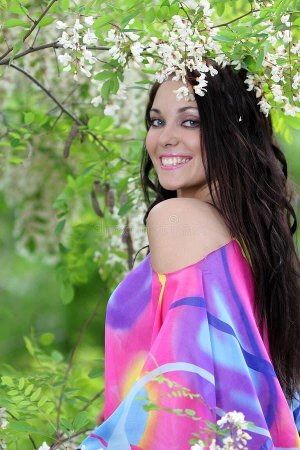 Hübsche lächelnde Mädchenentspannung im Freien in den Blumen lizenzfreie stockfotografie