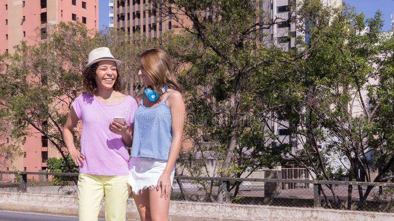Hübsche Mädchen im städtischen Hintergrund mit buildingsduring hellem Licht des Sommers Konzept der Freundschaft, aktive Leute, F stockbild