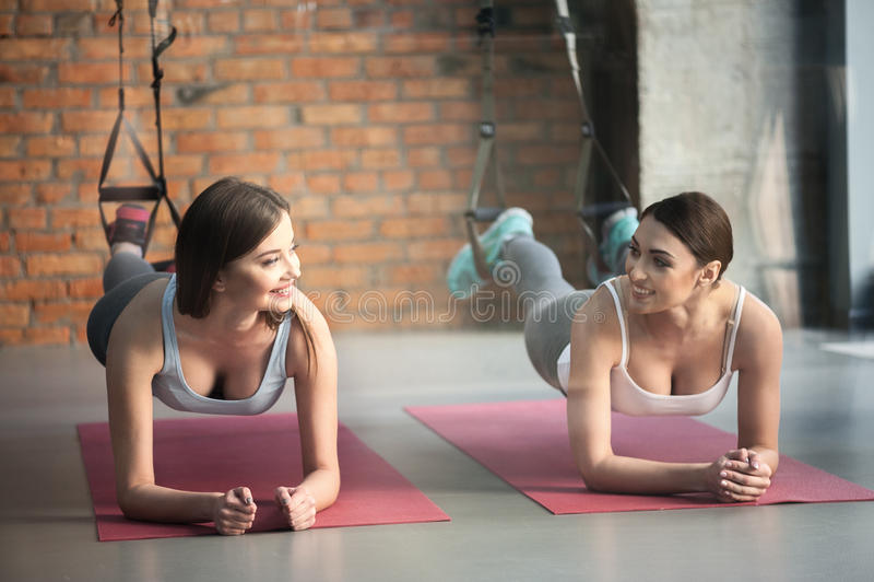 Hübsche Mädchen tun Plankenübung auf trx Bügeln stockfotografie