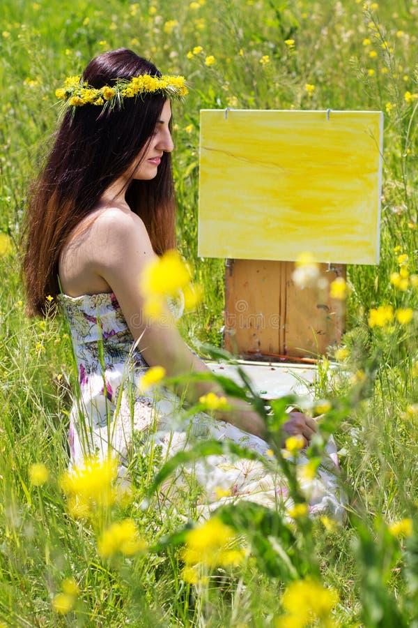 Hübsche Malermädchenmalerei auf dem gelben Gebiet stockfotografie