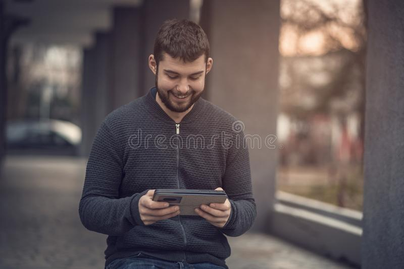 Hübsche Mitteilung des jungen Mannes ein Freund auf seiner Tablette in einem Stadtgebiet stockfoto