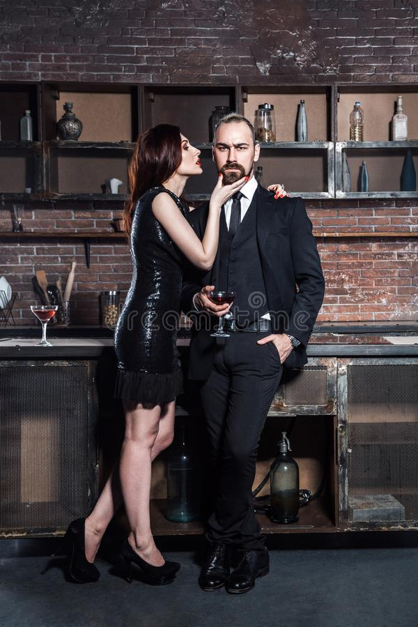 Hübsche Modepaare, die an einer Partei trinken lizenzfreie stockfotos