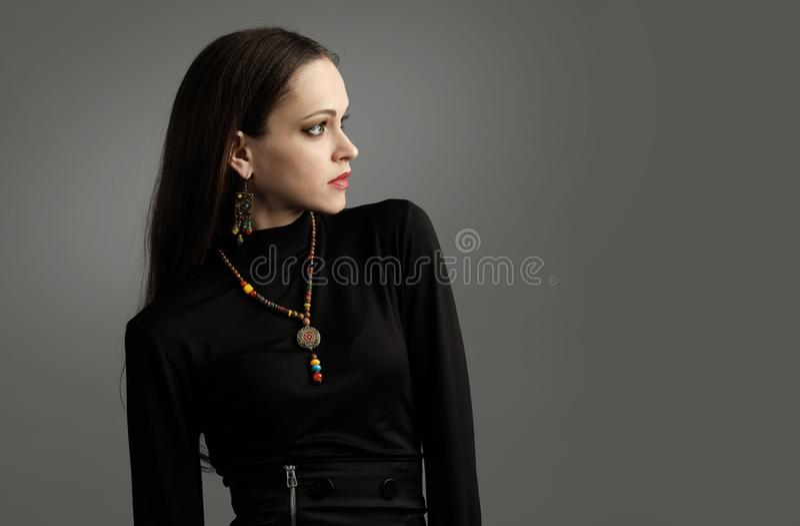 Hübsche moderne Frau, die schwarze Kleidung und Schmuck trägt lizenzfreie stockfotografie