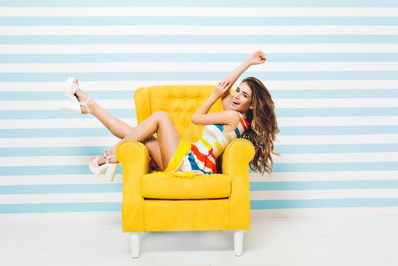 H?bsche moderne junge Frau im bunten Kleid mit dem langen gelockten brunette Haar, das Spa? im gelben Stuhl an lokalisiert hat stockbilder