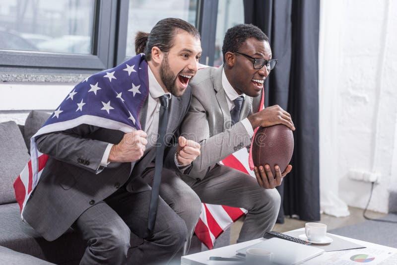 hübsche multiethnische Männer in den Klagen mit amerikanischer Flagge auf Schultern amerikanisches Fußballspiel aufpassend stockfotos