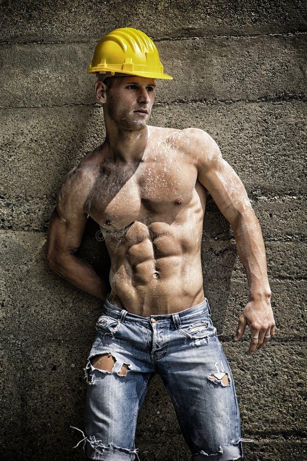 Hübsche muskulöse Bauarbeiterstellung stockfotos
