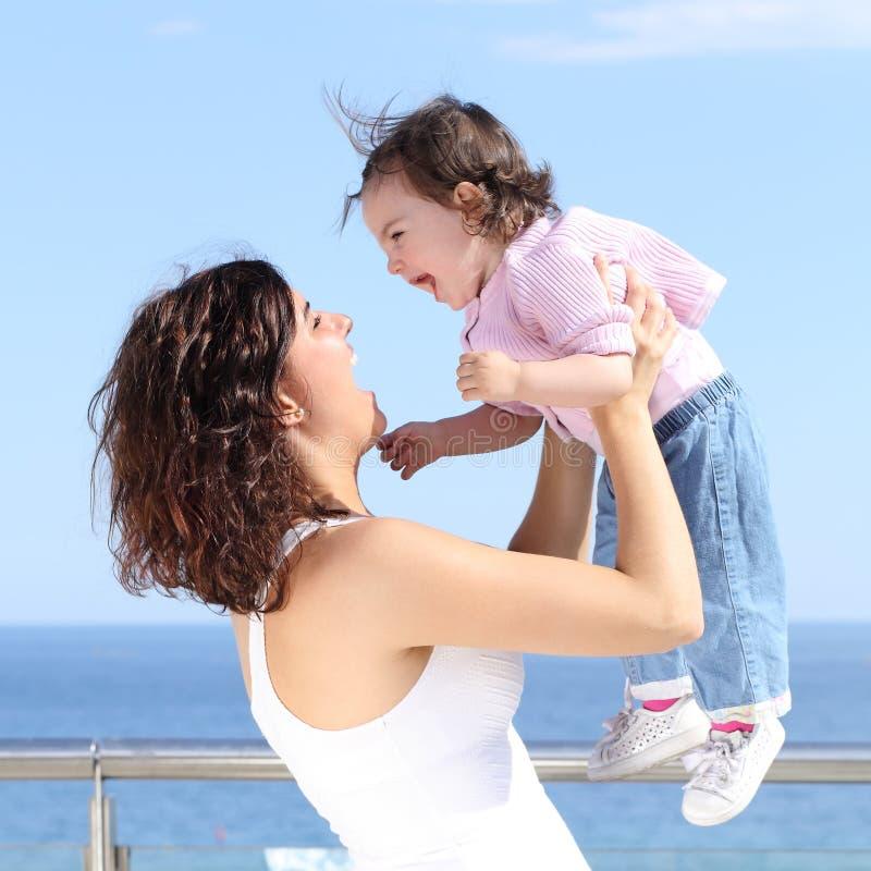 Hübsche Mutter, die ihr Baby lacht und aufzieht lizenzfreie stockbilder
