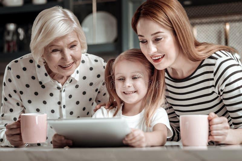 Hübsche nette Familie, die den Schirm der modernen Tablette lächelt und betrachtet stockbilder