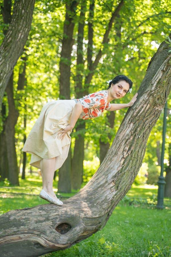 Hübsche nette junge brunette Frau, die mit ihrem reizenden Baum im grünen Sommergarten allein aufwirft glückliches Mädchenvergnüg lizenzfreie stockfotografie