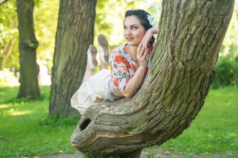 Hübsche nette junge brunette Frau, die mit ihrem reizenden Baum im grünen Sommergarten allein aufwirft glückliches Mädchenvergnüg stockfoto