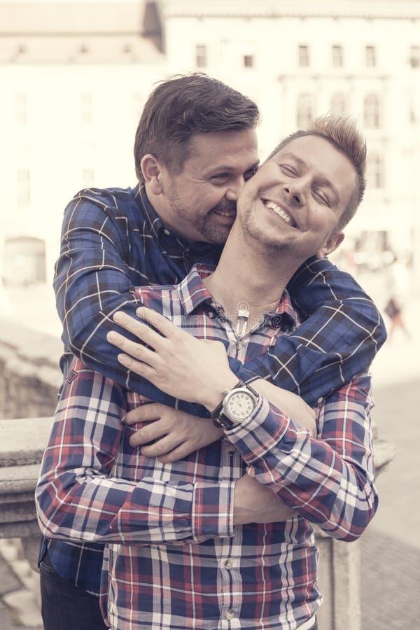 Hübsche Paare der homosexuellen Männer, die in der Stadt sich umarmen stockfotografie