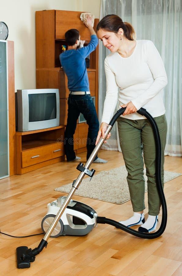 Hübsche Paare, die zusammen Hausarbeit tun lizenzfreie stockfotos
