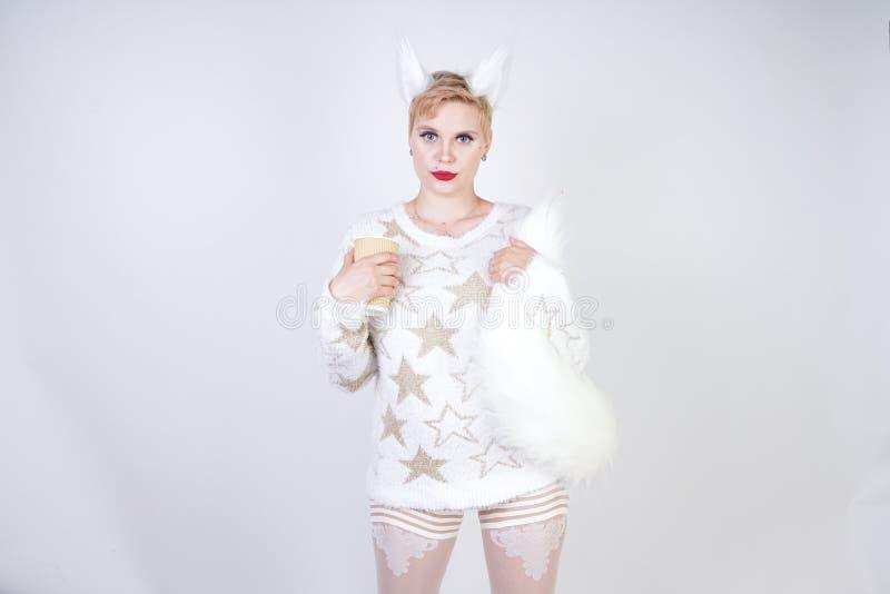Hübsche Pluswearng Frau der größe kaukasische Mode gestrickte warme Strickjacken- und Pelzkatzenohren und Aufstellung auf weißem  stockfotos