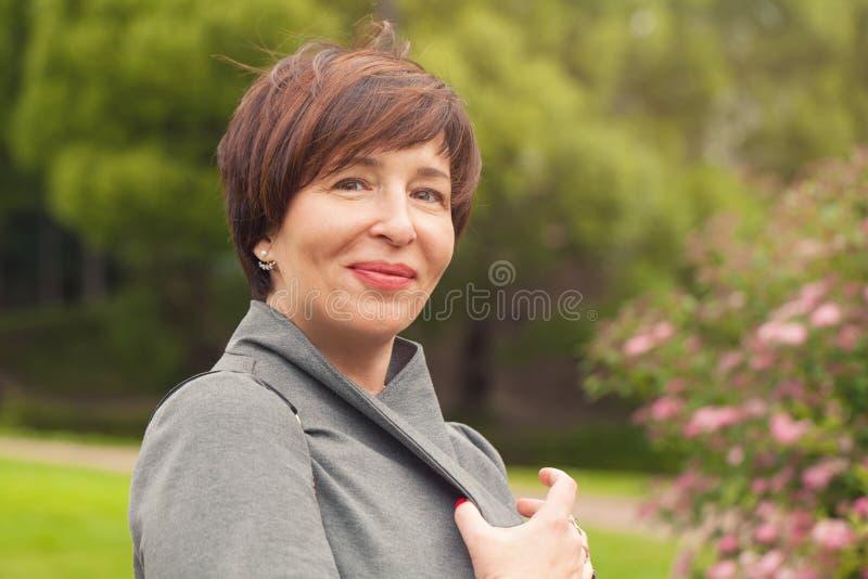 Hübsche reife Frauenentspannung im Freien lizenzfreie stockbilder