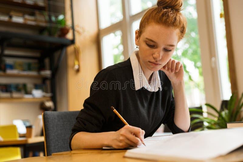 Hübsche rote behaarte Jugendliche, die am Tisch studiert stockfotografie