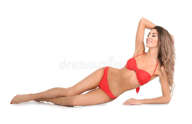 Hübsche sexy Frau mit schönem dünnem Körper im stilvollen Bikini, der auf Weiß liegt stockbilder