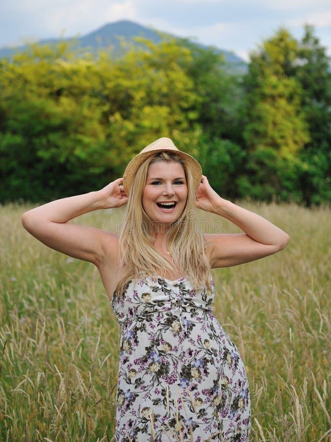 Hübsche Sommerfrau auf Weizenfeld in der Landschaft stockbild