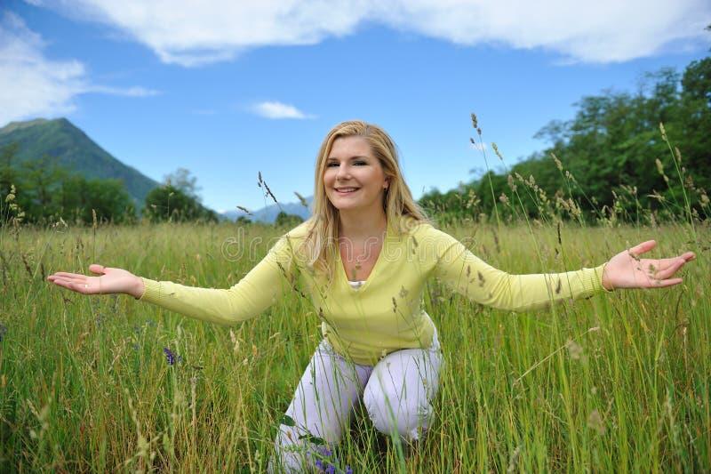Hübsche Sommerfrau draußen auf grünem Feld lizenzfreie stockbilder