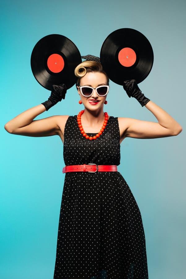 Hübsche Stift-obenfrau mit Retro- Frisur und dem Make-up, die mit Vinylaufzeichnung über blauem Hintergrund aufwirft lizenzfreie stockfotos
