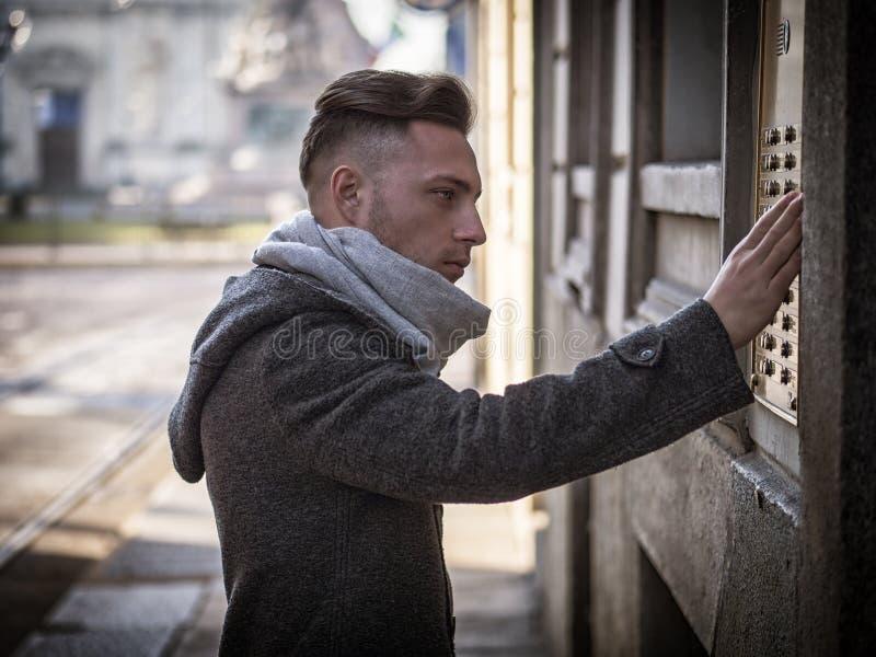 Hübsche stilvolle Klingelntürklingel des jungen Mannes am Gebäude stockfoto