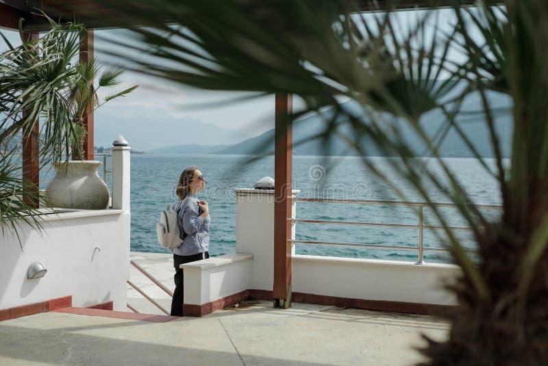 Hübsche touristische Frau genießt die Ansicht des Meeres und der Berge herein lizenzfreies stockfoto