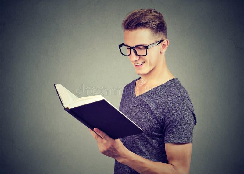 Hübsche tragende Gläser des jungen Mannes des Porträts, die ein Buch lesen lizenzfreies stockfoto