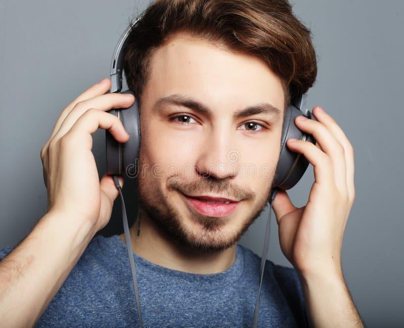 Hübsche tragende Kopfhörer des jungen Mannes und Hören Musik lizenzfreie stockfotos