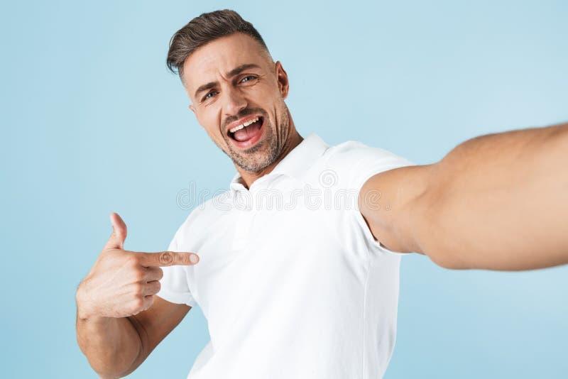 Hübsche tragende weiße Stellung T-Shirt des jungen Mannes stockbild