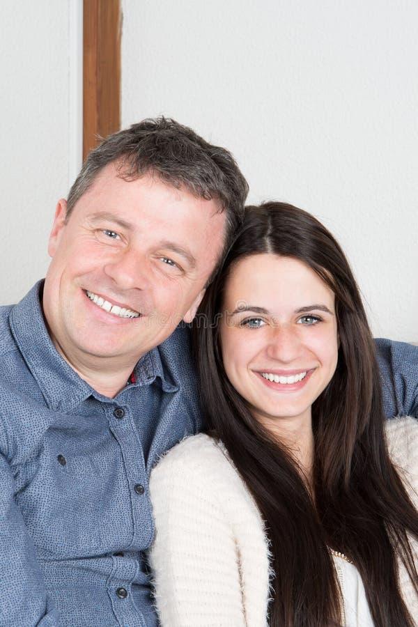 hübsche Vater- und Jugendlichtochter, die Kamera und das Lächeln betrachtend umarmt stockbild