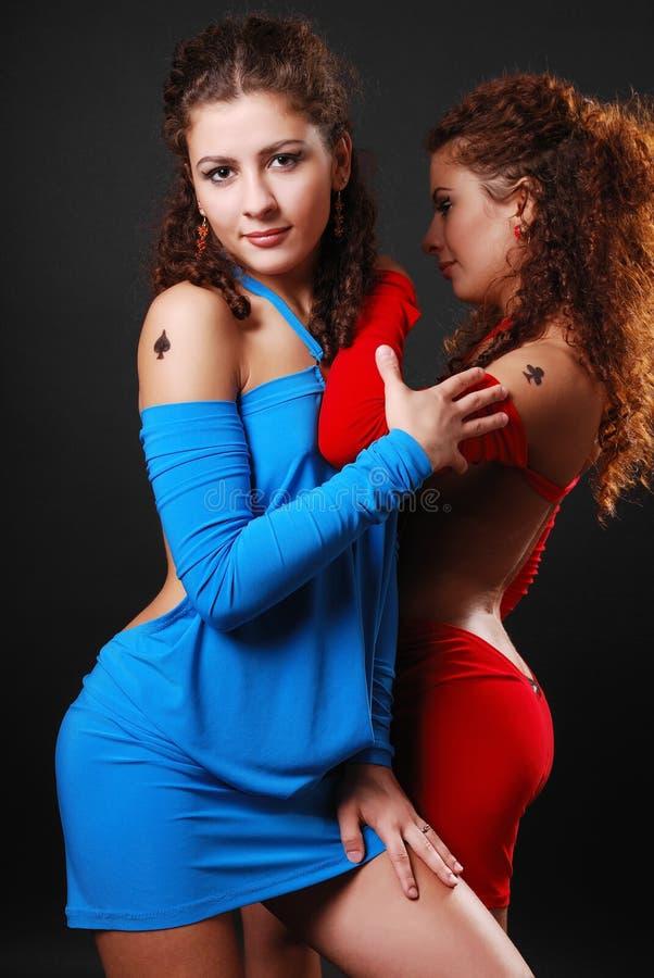 Hübsche Zwillinge, die im Cocktailkleid umarmen. lizenzfreie stockbilder